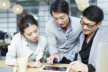 a team of young asian entrepreneurs discussing business in office using tablet computer